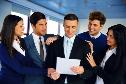 Happy colleagues congratulating businessman in office